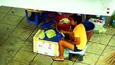 Mädchen bereitet Ware zum Verkauf vor in Bangkok 01